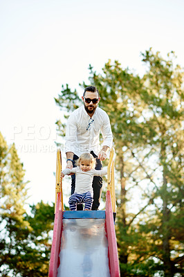 Buy stock photo Full length shot of a father and daughter on a slide in the park
