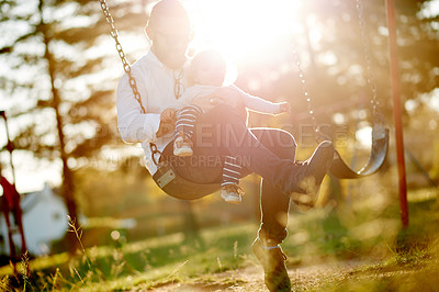 Buy stock photo Full length shot of a father and daughter on a swing in the park
