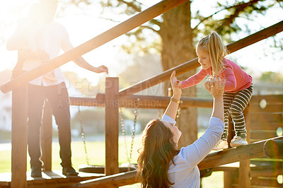 Buy stock photo Cropped shot of a young family on a jungle gym in the park