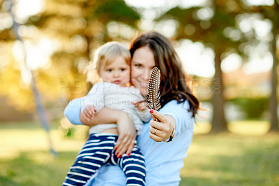 Buy stock photo Cropped shot of a mother holding her daughter and showing you a feather in the park