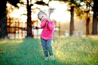 Buy stock photo Shot of an adorable little girl standing in a field of grass at the park