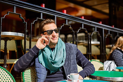 Buy stock photo Shot of a stylish young man talking on a cellphone while sitting at a table outside at a sidewalk cafe