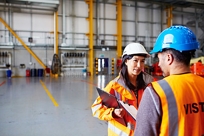 Buy stock photo Shot of two warehouse workers talking together over a clipboard