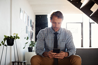 Buy stock photo Shot of a businessman sending a text message while sitting at home