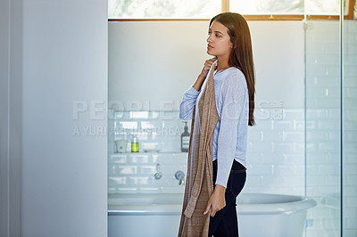Buy stock photo Shot of a young woman standing in her bathroom trying on an outfit