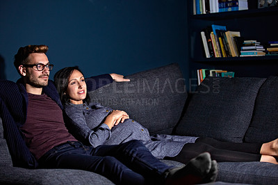 Buy stock photo Shot of a pregnant woman and her husband sitting on the sofa watching television in the evening