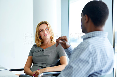 Buy stock photo Shot of two colleagues talking together in a modern office