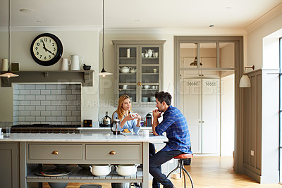 Buy stock photo Shot of a young couple sitting together at their kitchen table at home