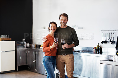 Buy stock photo Portrait of a smiling mature couple drinking wine together in their kitchen