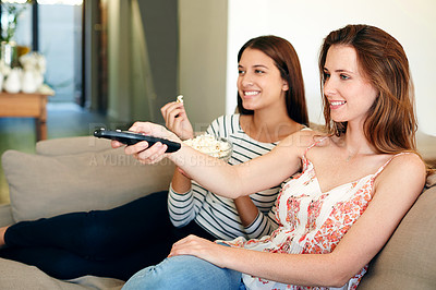 Buy stock photo Shot of two friends watching a movie together on the sofa at home