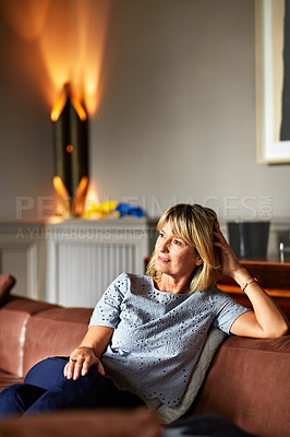 Buy stock photo Shot of a mature woman relaxing on her living room sofa