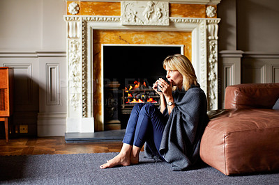 Buy stock photo Shot of a mature woman sitting against her sofa drinking tea while wrapped in a blanket