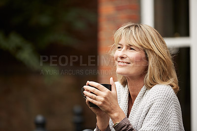 Buy stock photo Shot of a mature woman drinking a cup of coffee on her porch
