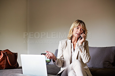 Buy stock photo Shot of a mature businesswoman sitting on a hotel bed using a laptop and cellphone