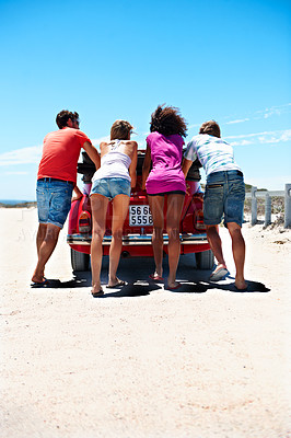 Buy stock photo Rearview shot of a group of friends pushing their car along a beach