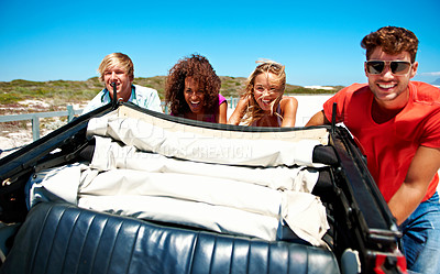 Buy stock photo Shot of a group of friends pushing their car along a beach