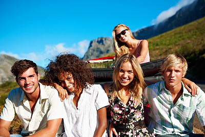 Buy stock photo Portrait of a group of friends sitting on their car bumper while on a road trip