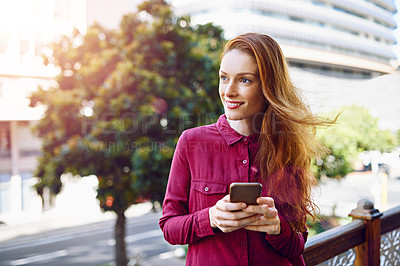Buy stock photo Shot of a young woman sending a text message while standing outside
