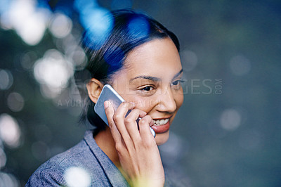 Buy stock photo Shot of a young woman talking on her cellphone in an office