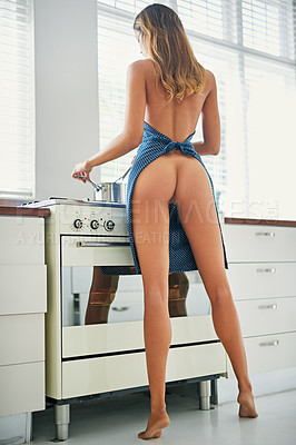 Buy stock photo Shot of a gorgeous young woman cooking at home in the nude