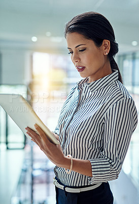 Buy stock photo Cropped shot of a young businesswoman working on a digital tablet in an office