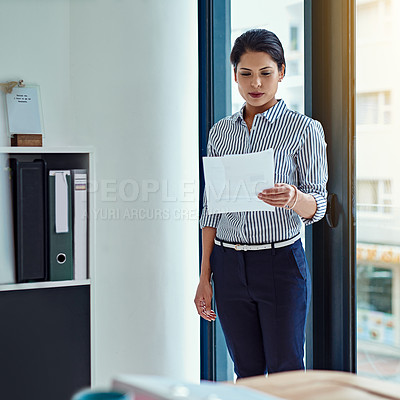 Buy stock photo Shot of a young businesswoman looking through some paperwork in an office