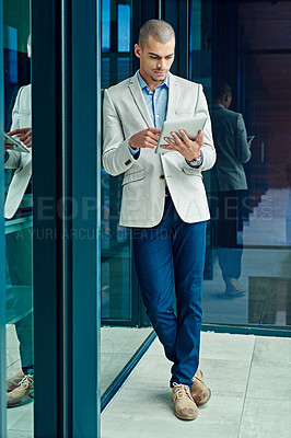 Buy stock photo Shot of a young businessman using a digital tablet at work