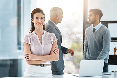 Buy stock photo Cropped portrait of a businesswoman standing in the office with her colleages in the background