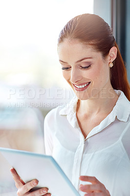 Buy stock photo Shot of a happy young businesswoman using a digital tablet at work