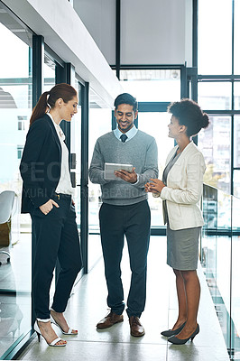 Buy stock photo Shot of a diverse group of young colleagues using a digital tablet together at work
