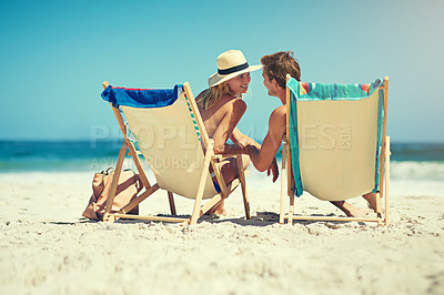 Buy stock photo Rearview shot of a young couple sitting on loungers at the beach