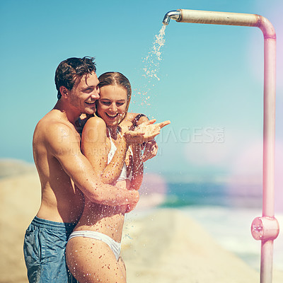 Buy stock photo Cropped shot of an affectionate young couple showering on the beach