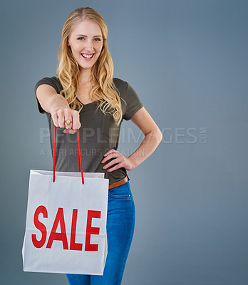 Buy stock photo Cropped studio shot of a young woman holding up a shopping bag with the word