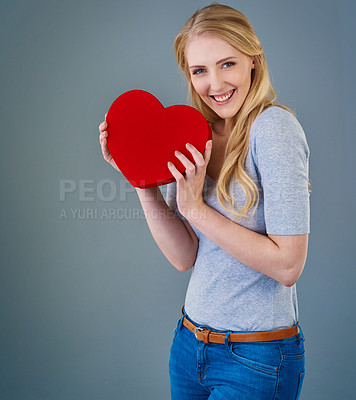 Buy stock photo Cropped studio shot of a young woman holding a red heart-shaped box