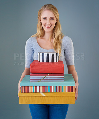 Buy stock photo Cropped studio shot of a young woman holding a stack of presents