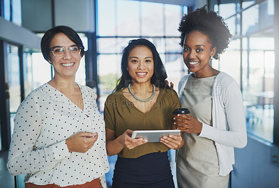 Buy stock photo Cropped portrait of three businesswomen looking at a tablet in the office