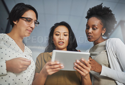 Buy stock photo Low angle shot of three businesswomen looking at a tablet in the office