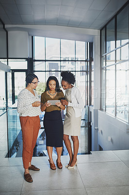 Buy stock photo Full length shot of three businesswomen looking at a tablet in the office