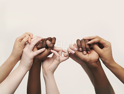 Buy stock photo Cropped shot of a group of hands reaching up and holding on to each other