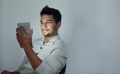 Buy stock photo Cropped shot of a young man using his tablet at night