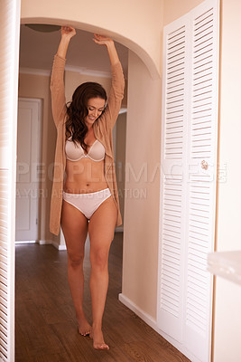 Buy stock photo Shot of a beautiful woman getting comfortable in her lingerie at home