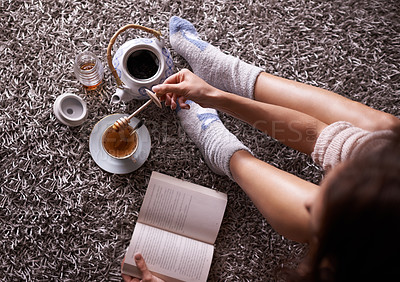 Buy stock photo High angle shot of a woman having tea while reading a book