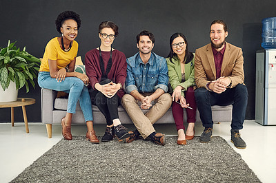 Buy stock photo Portrait of a group of young creatives sitting together on a couch in an office
