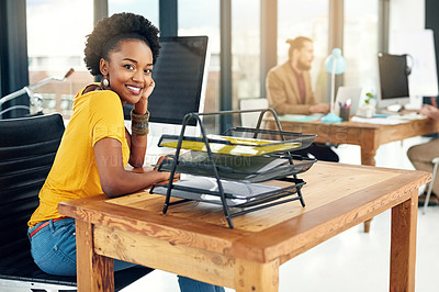 Buy stock photo Portrait of a young businesswoman sitting in an office with colleagues in the background