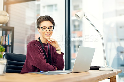 Buy stock photo Portrait of a young businesswoman working on a laptop in a modern office
