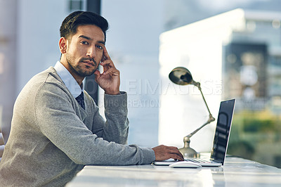 Buy stock photo Cropped portrait of a young businessman working on his laptop