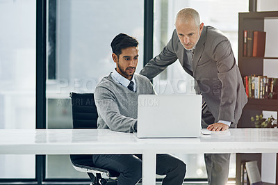 Buy stock photo Cropped shot of two businessmen working on a laptop in their office