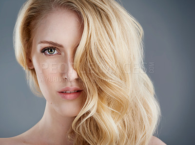 Buy stock photo Studio portrait of an attractive young woman with beautiful blonde hair posing against a gray background