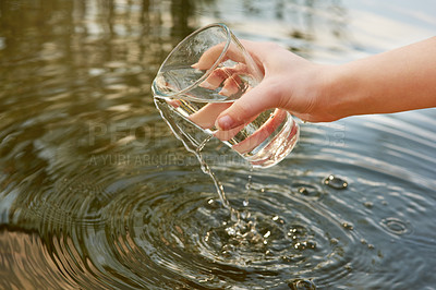 Buy stock photo Cropped shot of water being poured out from a glass into a pond