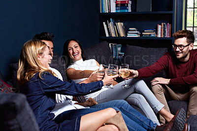 Buy stock photo Shot of a group of friends making a toast while enjoying a night in together at home